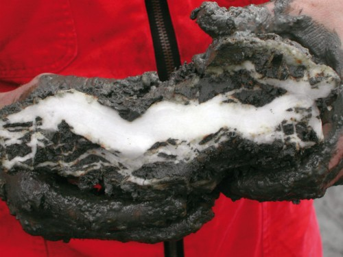 "2.16 > Methane hydrate looks like a piece of ice when it is brought up from the sea floor. This lump was retrieved during an expedition to the ""hydrate ridge"" off the coast of Oregon in the US. © dpa Picture-Alliance/MARUM"