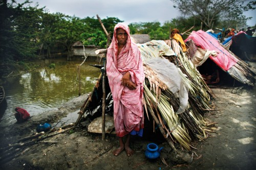 3.12 > Bangladesh experienced the full force of Cyclone Aila in 2009. Thousands of people lost their homes. This woman saved herself and her family of five in a makeshift shelter after the gushing waters burst a mud embankment.