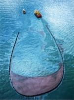 """4.16 > Mit einer Kette aus aufblasbaren Schwimmern versucht ein Spezialschiff Rohöl einzufangen, das der Öltanker """"Sea Empress"""" verloren hat, nachdem er 1996 vor der Küste von Wales auf Grund gelaufen war. Bei rauer See ist der Einsatz solcher Ölskimmer allerdings oft wirkungslos. Abb. 4.16: ©David Woodfall/Getty Images"""