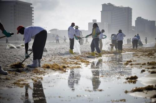 """4.19 > Gleich säckeweise sammeln  Arbeiter am Strand des beliebten US-Seebads Gulf Shores ölverklebte Algenmassen zusammen. Der Ort an der Küste des Bundesstaats Alabama gehört zu jenen Gemeinden am Golf von Mexiko, die im Juni 2010 durch  Öl aus der havarierten Plattform """"Deepwater Horizon"""" verschmutzt worden sind.  ©Xinhua/Landov/inter TOPICS"""