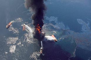 """Abb. 1.35 > Nach der Explosion am 20. April 2010 brannte die Bohrplattform """"Deepwater Horizon"""" noch mehrere Tage lang. Versuche, sie mit Wasserkanonen zu löschen, schlugen fehl. schließlich kenterte die Insel und versank im Golf von Mexiko. © Gerald Herbert/picture alliance/AP Images"""