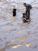 """Abb. 4.12 > Bei der Havarie des Tankers """"Hebei Spirit"""" vor Südkorea im Dezember 2007 wurden etliche Kilometer der Küste verschmutzt. Die Behörden mobilisierten 12000 Helfer, die das Öl mitunter mit einfachster Ausrüstung wie Eimer und Schaufel zu beseitigen versuchten. Die Kosten solcher Reinigungsarbeiten sind immens. © Kim Jae Hwan/AFP/Getty Images"""