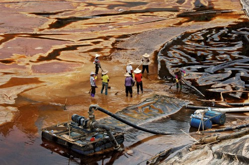 fig. 4.8 > In July 2010, a waste tank at a copper mine in the coastal province of Fujian in China burst open, spilling toxic slurry into a river and killing 1900 tonnes of fish. © Stringer China/Reuters