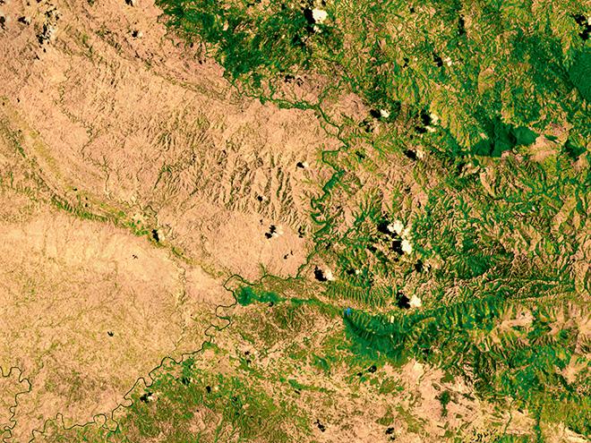 Abb. 2.25 > Grenzfluss zwischen Haiti (linke Seite) und Dominikanischer Republik. Die Armut hat dazu geführt, dass Haiti fast völlig entwaldet wurde. In der Dominikanischen Republik hingegen blieb der Wald zu einem Teil erhalten, wodurch die Bevölkerung besser vor Hurrikans geschützt ist. © NASA/ Goddard Space Flight Center Scientific Visualization Studio