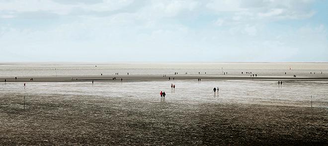 Abb. 1.25 > Das Wattenmeer der Nordsee ist bei Touristen sehr beliebt. Viele Menschen sind fasziniert, wenn sie zum ersten Mal bei Ebbe über den schlickigen Meeresboden wandern. © Thomas Ebert/laif