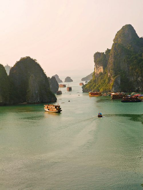 fig. 1.27: The karst cliffs in the Ha Long Bay in Vietnam are world famous. Tourists ride on boats through the archipelago. © mauritius images/imageBroker/Flavia Rad- davero