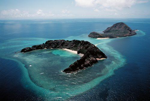 """Abb. 2.24: Die von einem Korallenriff eingefasste Wyer Island liegt in der Meerenge zwischen Australien und der Insel Neuguinea, der Torres Strait. Dieses Meeresgebiet wird von den Ureinwohnern als """"Salzwasserland"""" bezeichnet. Mit diesem Begriff ist sowohl die Landfläche der Inseln als auch das Meer mit seinen Korallenriffen gemeint. © Lincoln Fowler/Photographers Direct.com"""