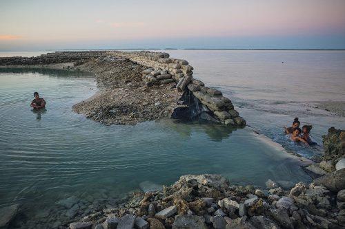 Abb. 4.14: Der Inselstaat Kiribati bemüht sich, seine flachen Atolle teils durch massive Mauern vor dem Meer zu schützen. In vielen Fällen aber zerstören Sturmfluten die Bauwerke, wie hier vor der Hauptstadt South Tarawa. © Vlad Sokhin/laif